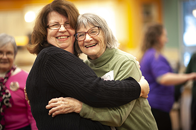 two women smiling and hugging