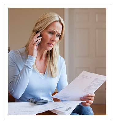 worried woman looking at a piece of paper while making a phone call