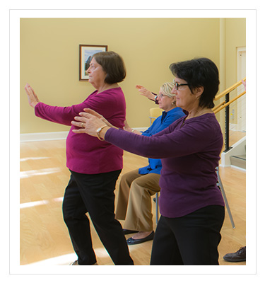 a group of women performing tai chi