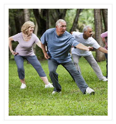 group of older adults performing tai chi in a park