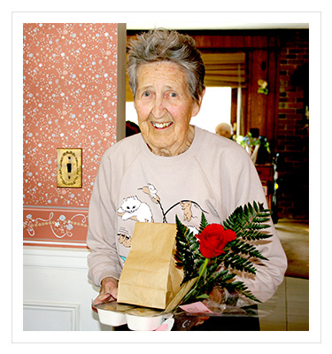 older woman holding a meal and a rose