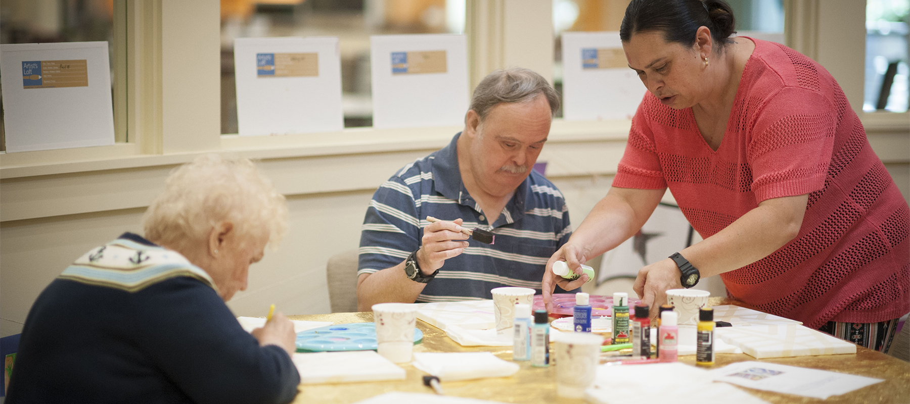 ... two older adults painting at a table while a woman offers assistance
