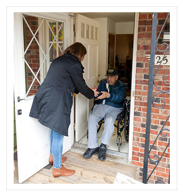 a woman delivering a meal to an older man in a wheelchair